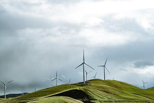 Wind Turbines on Green Grass Field Under White Cloudy Sky