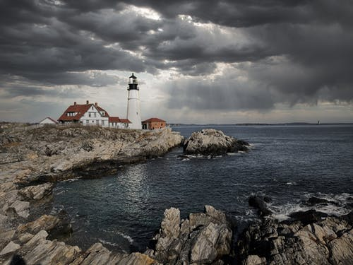 Amazing scenery of Portland Head Light lighthouse and small settlement located on rocky cliff above wavy sea under dramatic overcast sky