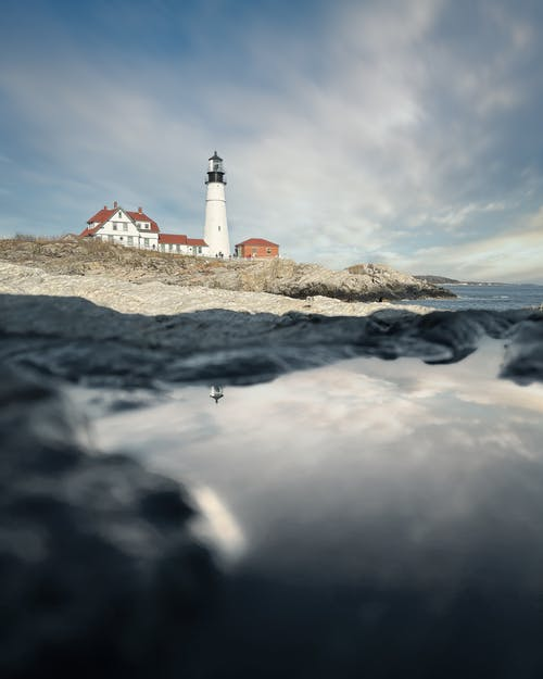 White lighthouse and cottages on rocky seashore against cloudy sky