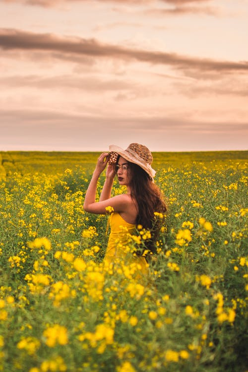 A Woman in Yellow Dress Standing in the Middle of Yellow Flower Field
