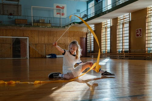 Girl Using Gymnastic Ribbon while Sitting on Wooden Floor