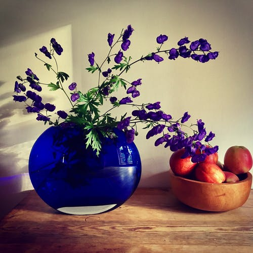Purple Petaled Flower Arrangement Near Apple Fruit on Table