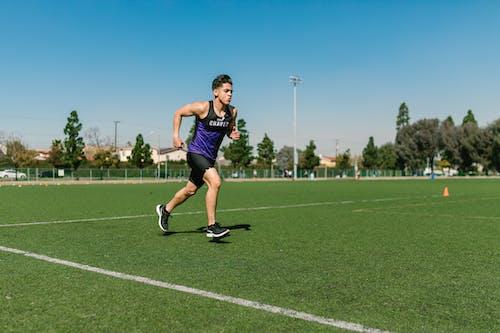 Woman in Black Tank Top Running on Green Field