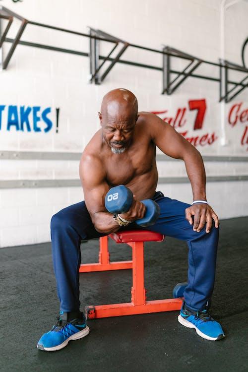 Shirtless Man Lifting Dumbbells while Sitting Down
