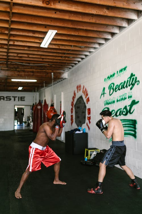 Two Men Practicing Boxing in a Gym