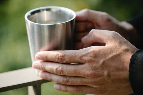 Photo of Person Holding Stainless Cup