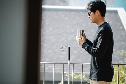 Photo of Man Drinking Coffee in the Balcony