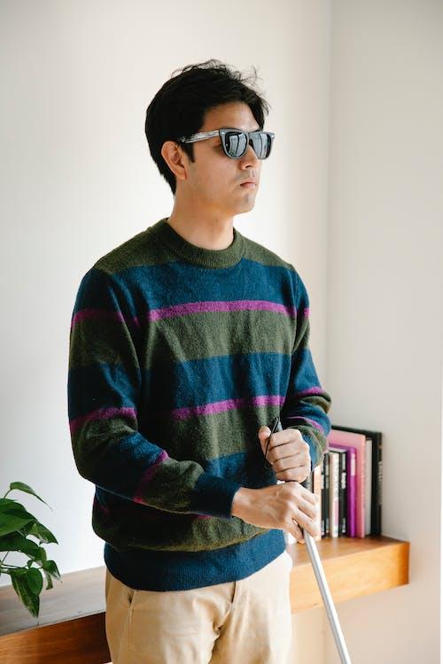 Photo of Man Standing Beside Wooden Desk