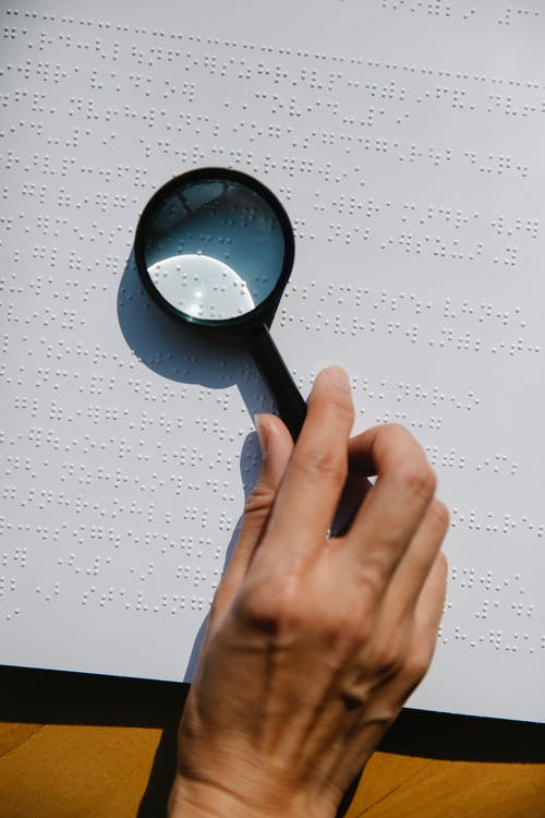 Photo of Person Holding Magnifying Glass