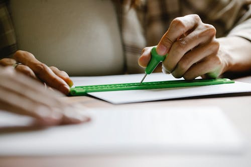 Close-Up Photo Of Person Using Stylus And Slate