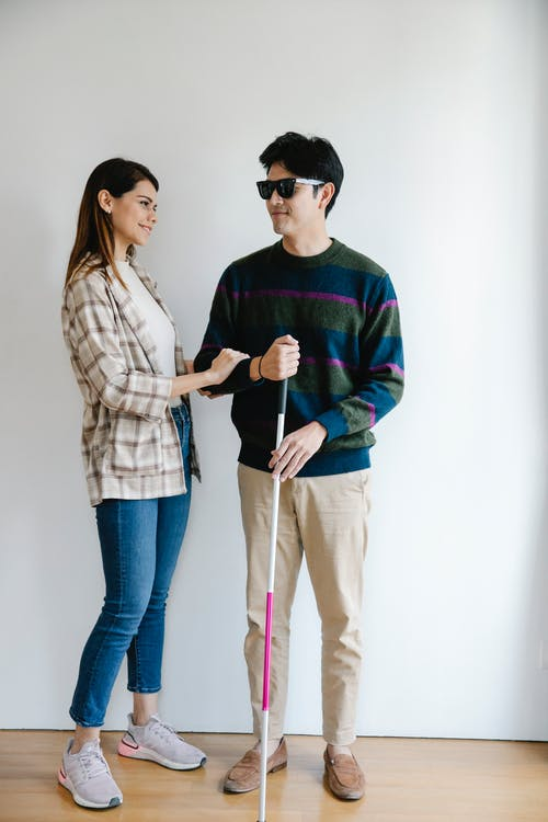 Photo of Woman Gladly Assisting Man