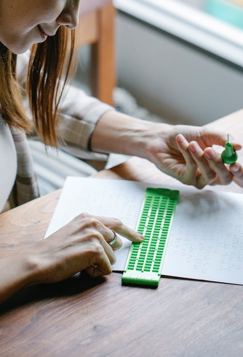 Close-Up Photo of Woman Making Braille Caharacters