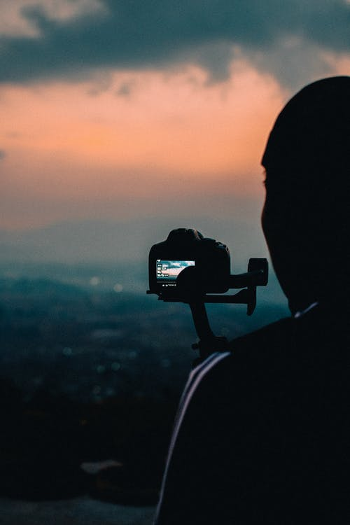 Silhouette of Man Taking Photo of Mountain during Sunset