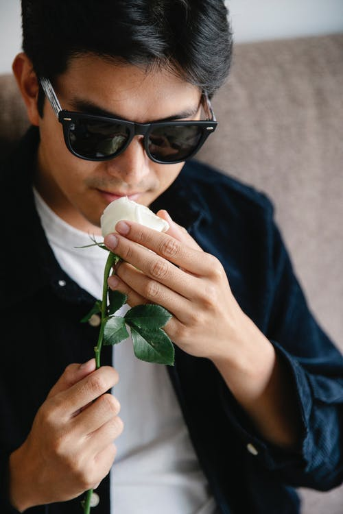 Photo Of Man Smelling White Flower