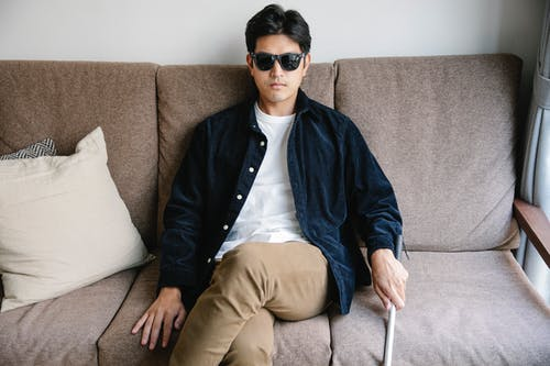 Photo Of Man Sitting On A Couch
