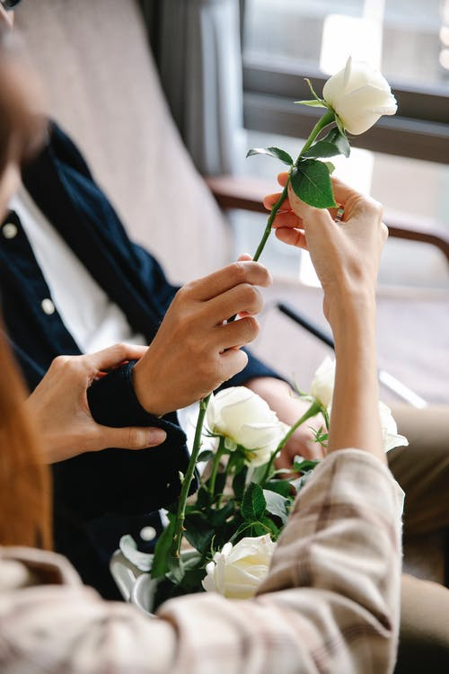 Close-Up Photo Of Couple Holding White Flower