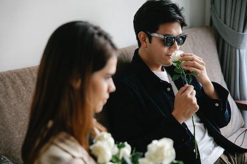 Photo of Man Smelling White Rose