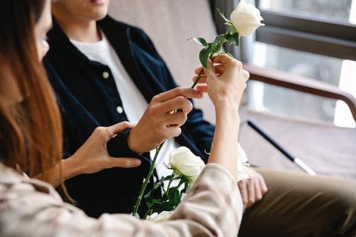 Photo Of Couple Holding A White Flower