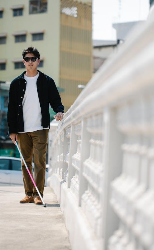 Photo Of Man Walking On Sidewalk
