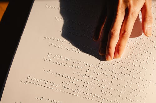 Close-Up Photo Of Person Using Braille