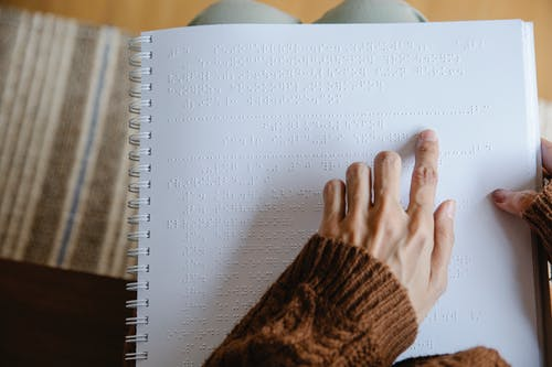 Photo of Person Using White Braille Paper