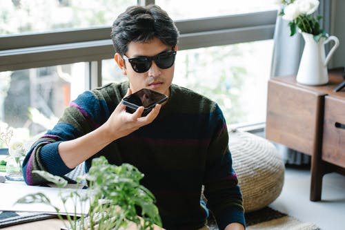 Photo of Man Holding Black Smartphone