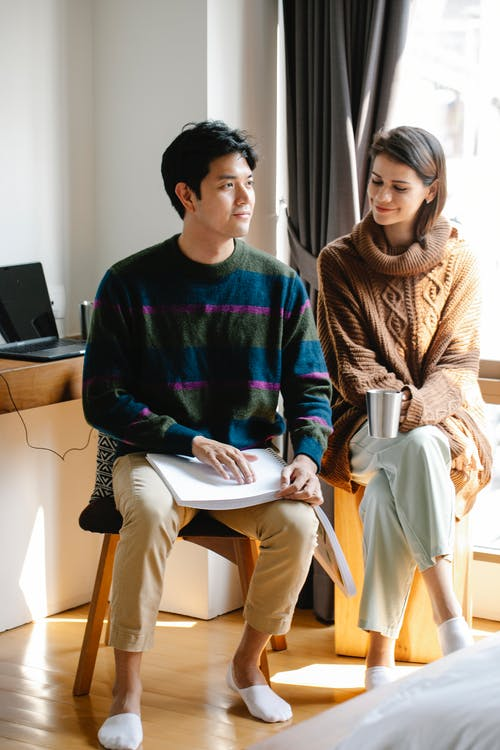 Photo of Woman Happily Sitting Beside Man
