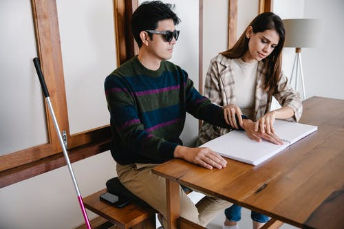 Photo of Woman Assisting Man for Braille Lessons