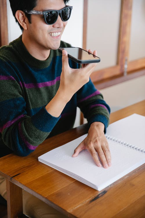Photo of Man Talking to the Phone while Studying Using Braille