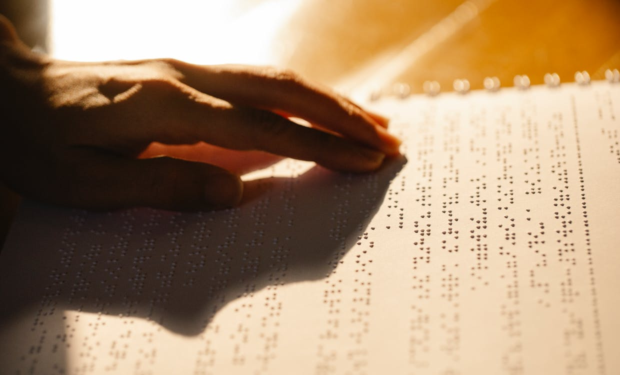 Close-Up Photo of Person Using Book for the Visually Impaired