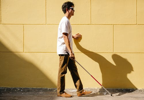 Photo of Man Walking on the Wall Side Using Cane