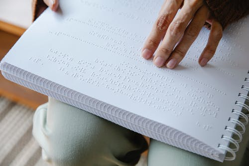 Photo of Person Holding White Braille Paper