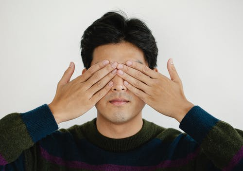 Photo of Man Covering his Eyes Using Hands