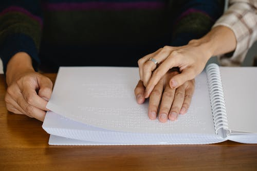 Photo of People Holding Hands on Top of Braille