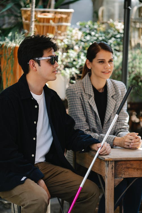 Photo of People Sitting Beside Wooden Table