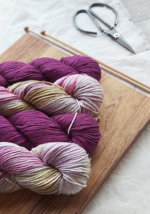 Purple and Pink Yarn on Brown Wooden Table
