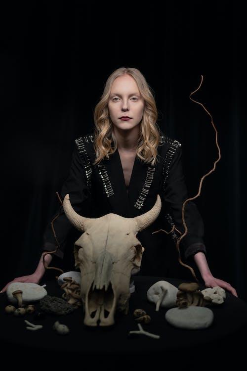Woman in Black Clothing Standing Beside White Animal Skull