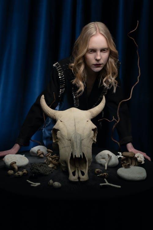 Woman in Black Robe Standing Beside White Animal Skull on the Table