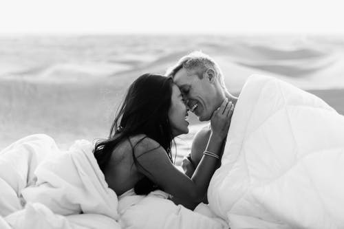 Black and white of positive couple smiling and embracing under white soft blankets on blurred background of desert