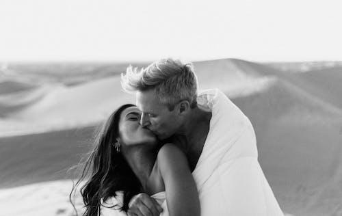 Loving happy couple kissing in dry desert