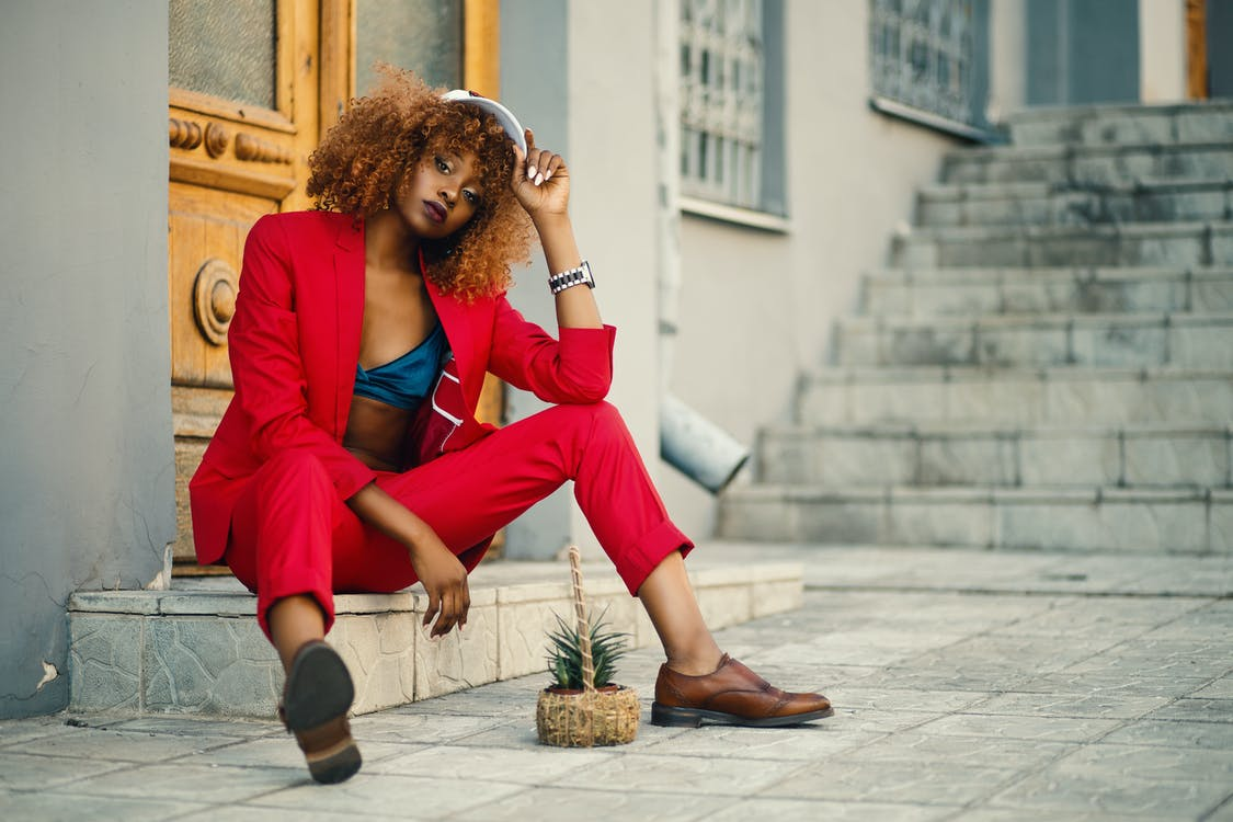 Woman Wearing Red Blazer and Pants Sitting on Marble Ground