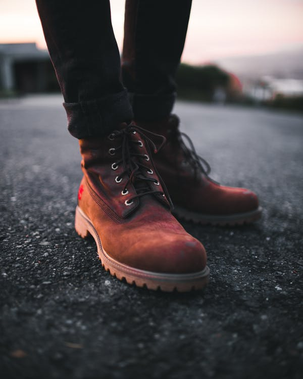 Person Wearing Pair of Brown Timberland Work Boots and Black Denim Skinny Jeans Standing on Asphalt Road