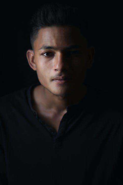 Crop Indian man in dark room