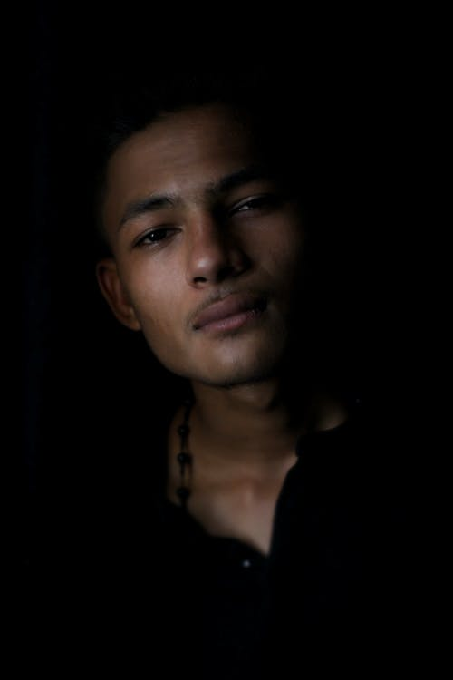 Young Indian confident man staring in darkness