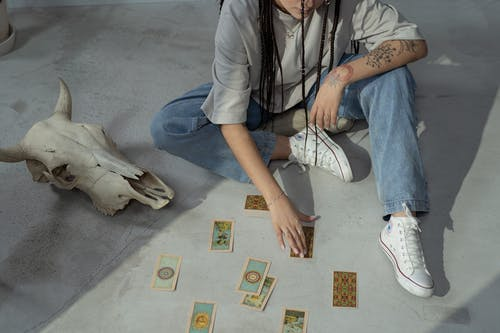 A Woman Holding a Tarot Card on the Floor
