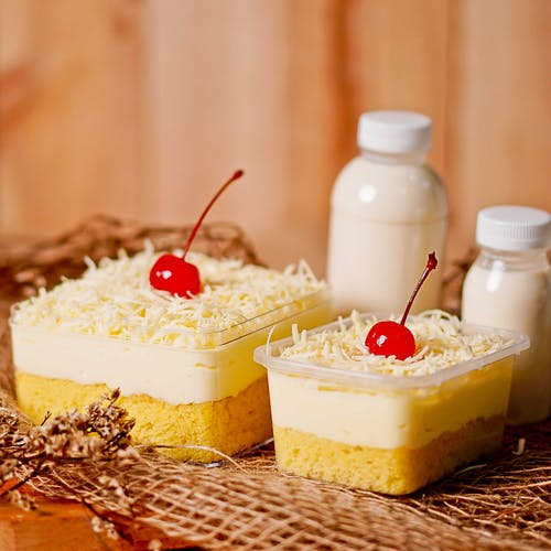 White and Yellow Cake With Cherry on Top