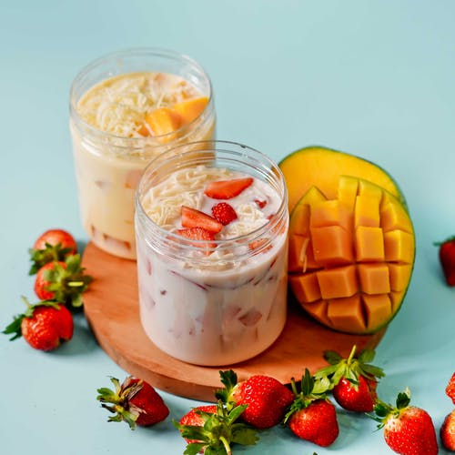 Fruit Salad with Yoghurt in Plastic Jars on Chopping Board Beside Mango