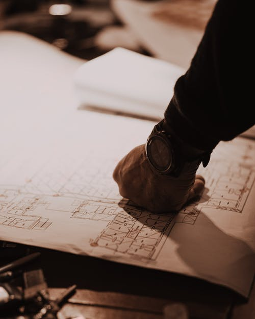 Man's Fist with Watch on Blueprint