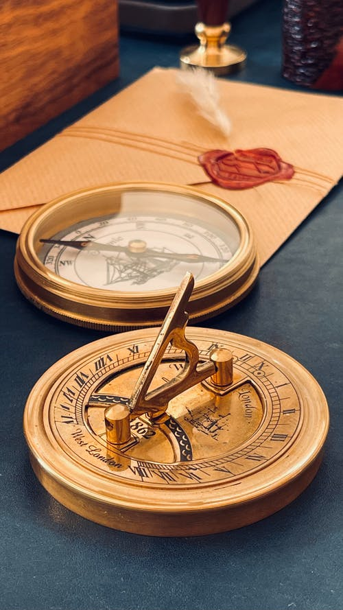Golden Sundial and Compass on Gray Table