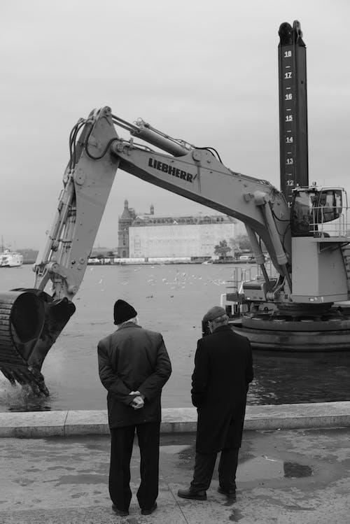 Men Standing Near Crane and Body of Water